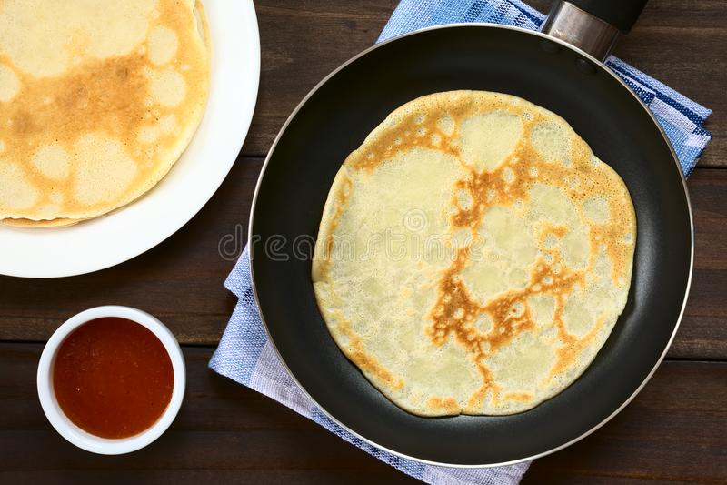 Homemade Crepe in Skillet. Freshly made crepe in frying pan with a stack of crepes and strawberry jam on the side, photographed overhead with natural light stock photos