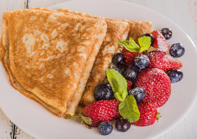 Homemade crepes with berries and fruit. On a white background stock photography