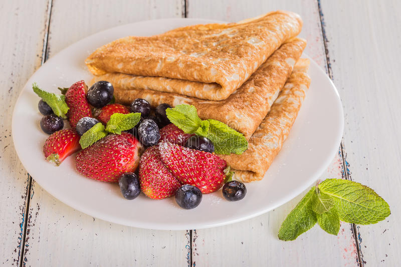 Homemade crepes with berries and fruit. On a white background royalty free stock photography
