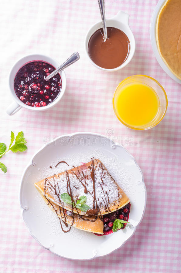 Homemade crepes with berries. Homemade pancakes with hot raspberries and blueberries royalty free stock photo