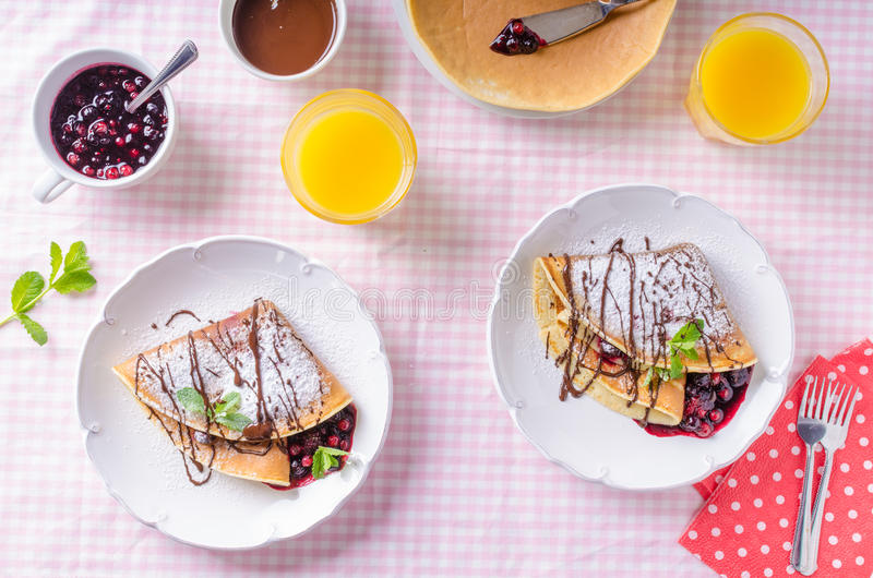 Homemade crepes with berries. Homemade pancakes with hot raspberries and blueberries royalty free stock images