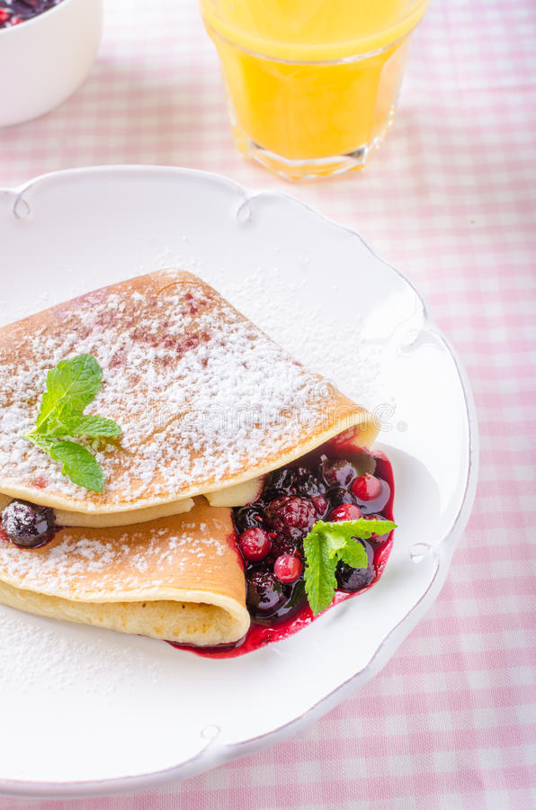 Homemade crepes with berries. Homemade pancakes with hot raspberries and blueberries stock image