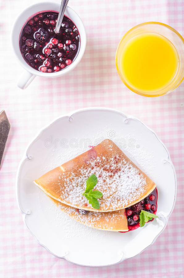 Homemade crepes with berries. Homemade pancakes with hot raspberries and blueberries stock photos