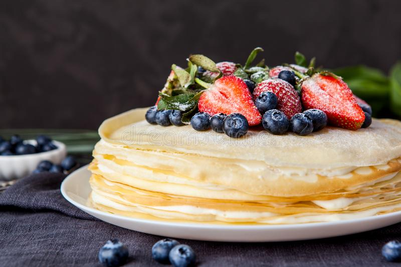 Crepes cake with cottage cheese and strawberry, selective focus. Homemade crepes cake with strawberry on rustic background. Cooking fresh homemade breakfast royalty free stock photo