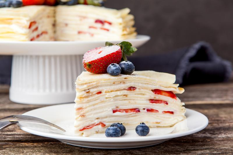 Crepes cake with cottage cheese and strawberry, selective focus. Homemade crepes cake with strawberry on rustic background. Cooking fresh homemade breakfast royalty free stock images
