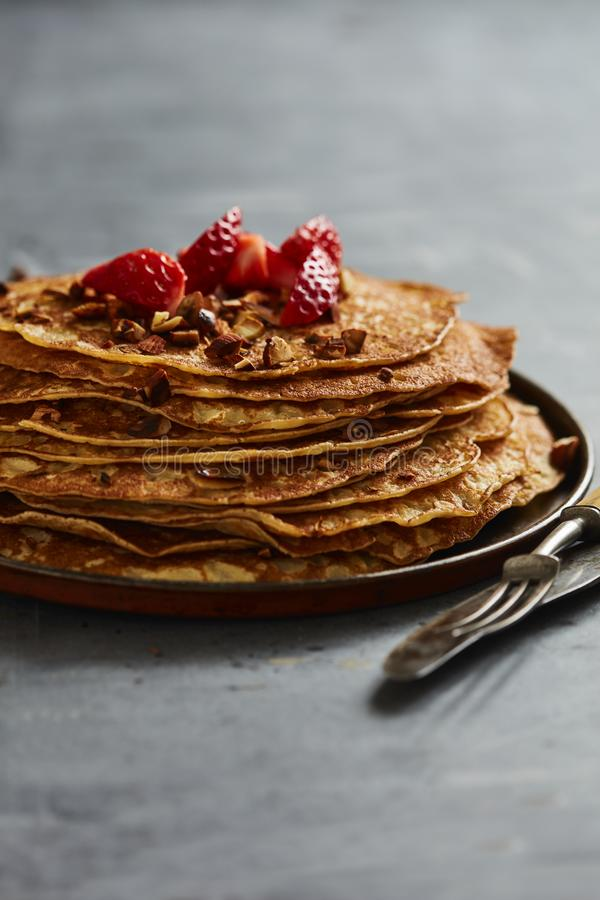 Crepes with strawberries and rosted almonds royalty free stock image