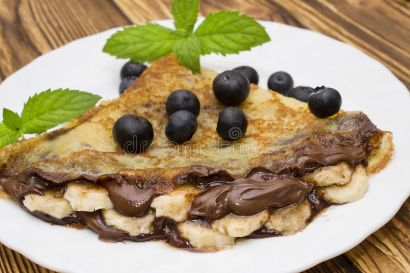 Homemade crepes with chocolate cream, banana and blueberries on white background. pancakes. Homemade pancakes with chocolate cream, banana and blueberries on royalty free stock photo