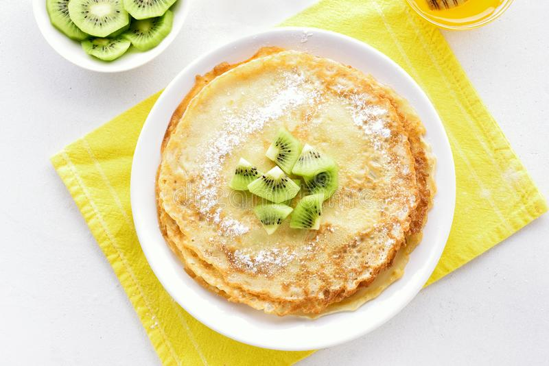 Crepes decorated with kiwi slices. Homemade crepes decorated with kiwi slices. Thin pancakes. Top view, flat lay stock images