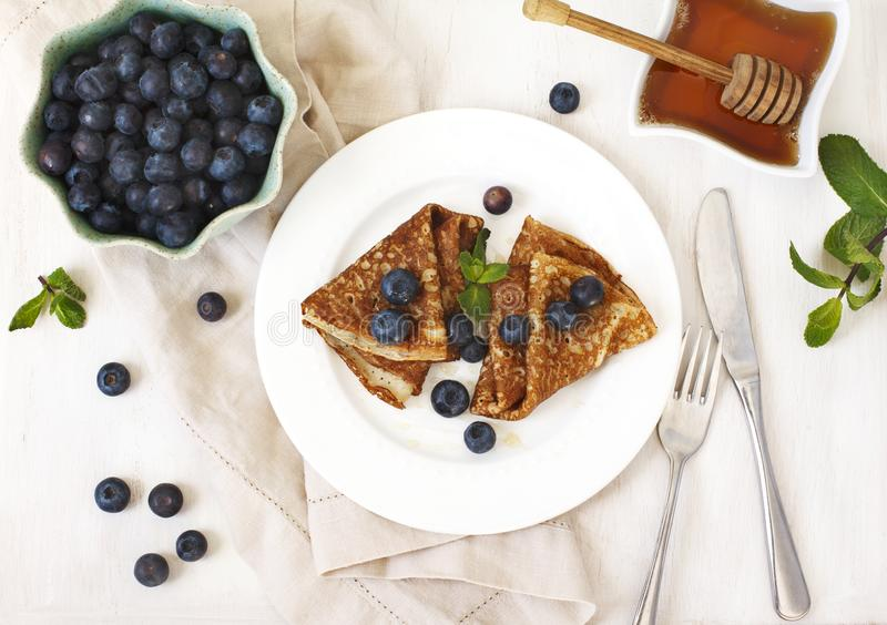 Homemade crepes with fresh blueberries and honey. Top view royalty free stock image