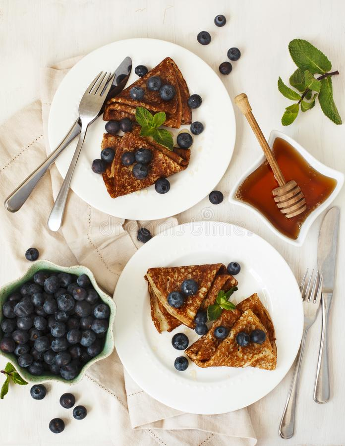 Homemade crepes with fresh blueberries and honey. Top view royalty free stock photography