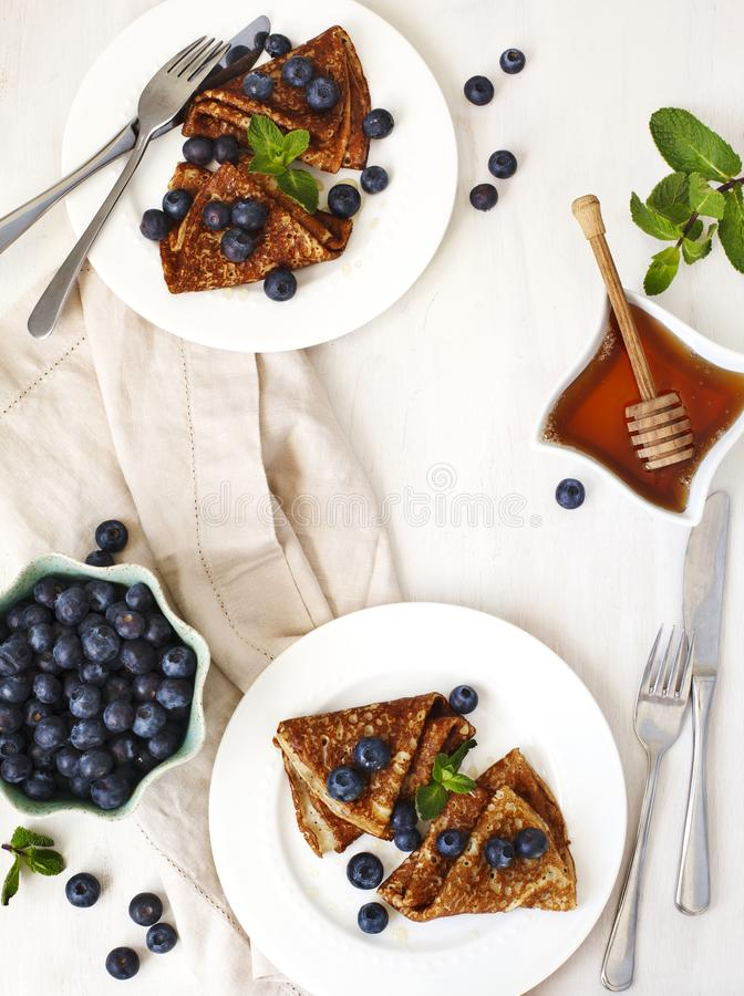 Homemade crepes with fresh blueberries and honey. Top view, copy space royalty free stock image