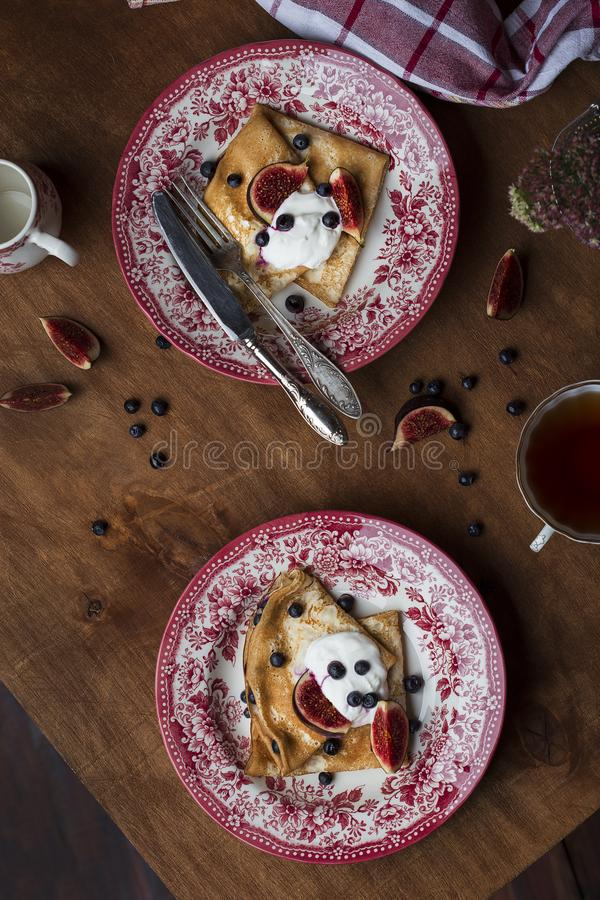 Homemade crepes with fresh figs blueberries and sour cream. Homemade golden crepes with fresh figs blueberries and sour cream stock photo