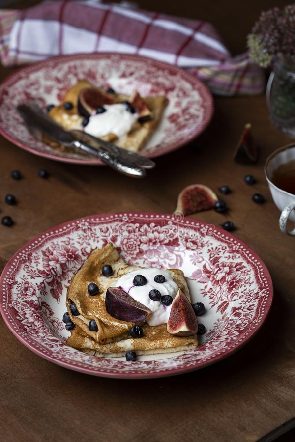 Homemade crepes with fresh figs blueberries and sour cream. Homemade golden crepes with fresh figs blueberries and sour cream royalty free stock photo