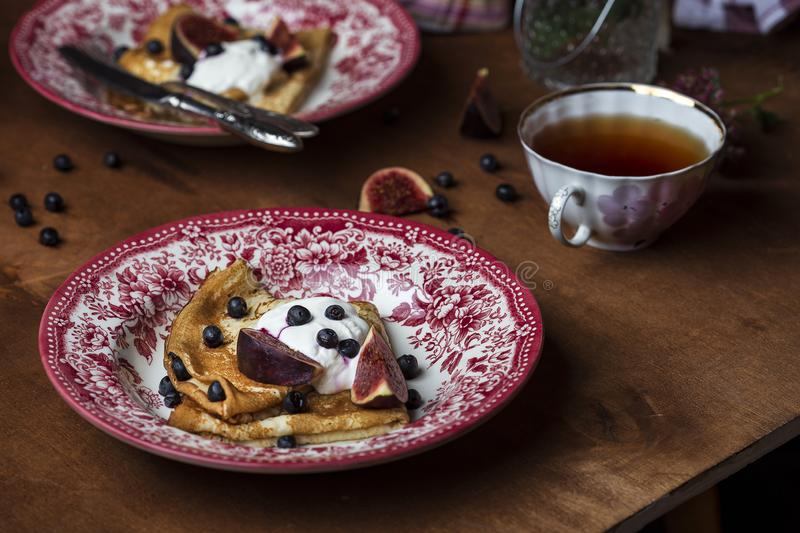 Homemade crepes with fresh figs blueberries and sour cream. Homemade golden crepes with fresh figs blueberries and sour cream stock images