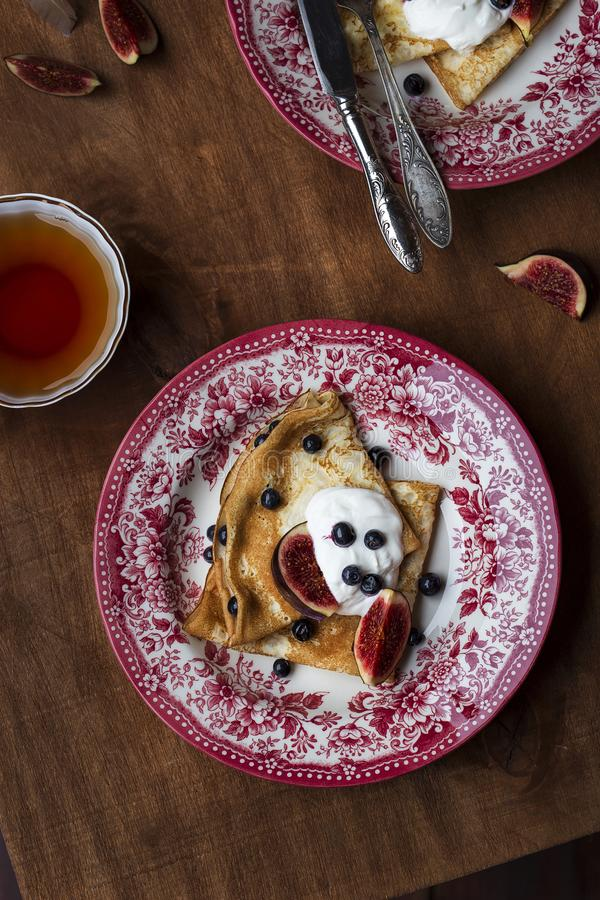 Homemade crepes with fresh figs blueberries and sour cream. Homemade golden crepes with fresh figs blueberries and sour cream royalty free stock images