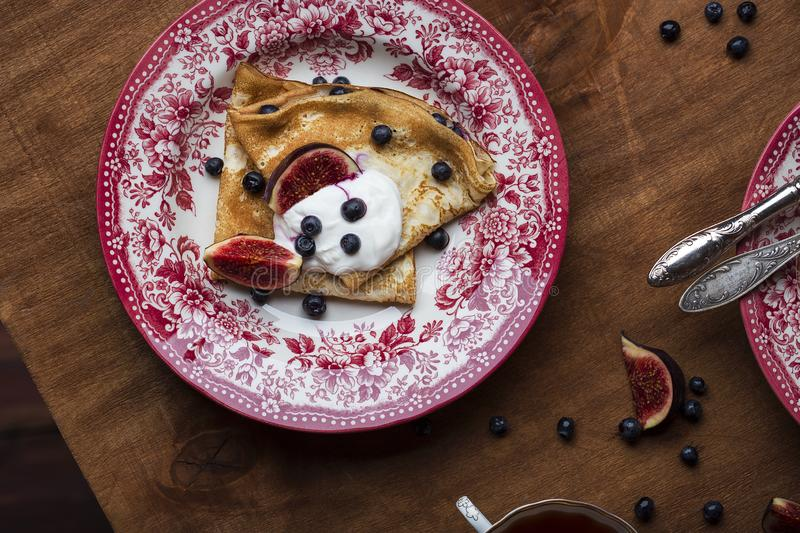 Homemade crepes with fresh figs blueberries and sour cream. Homemade golden crepes with fresh figs blueberries and sour cream royalty free stock photos