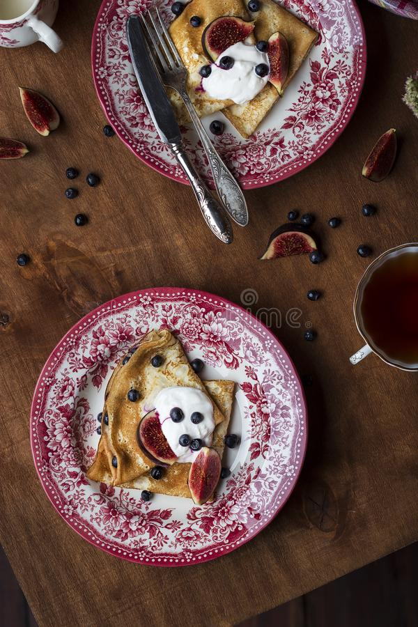 Homemade crepes with fresh figs blueberries and sour cream. Homemade golden crepes with fresh figs blueberries and sour cream royalty free stock image