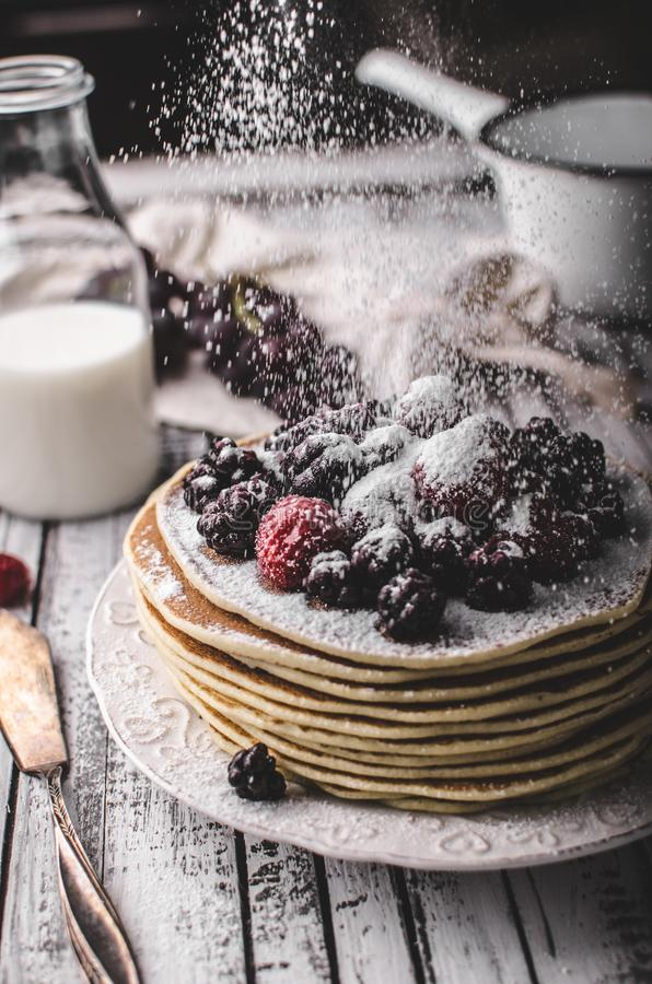 Homemade crepes with frozen berries, topped sugar. Rustic wood board, vintage photography royalty free stock photos