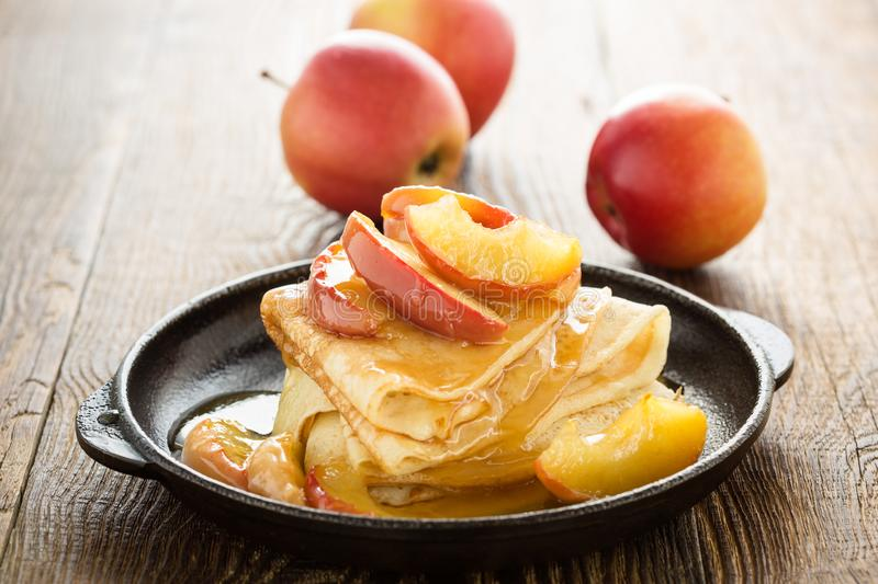 Homemade crepes served with caramelized apples. Homemade crepes served with fresh caramelized apples and caramel sauce in cast iron skillet on rural wooden table royalty free stock image