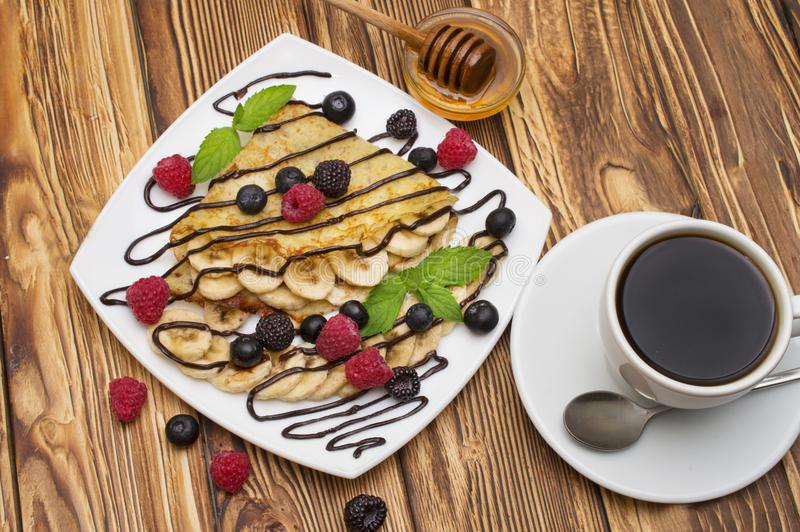 Homemade crepes served with chocolate cream, Banana, fresh blueberries, raspberries on a wooden background, pancakes.  royalty free stock photos