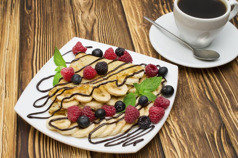 Homemade crepes served with chocolate cream, Banana, fresh blueberries, raspberries on a wooden background, pancakes.  royalty free stock photo
