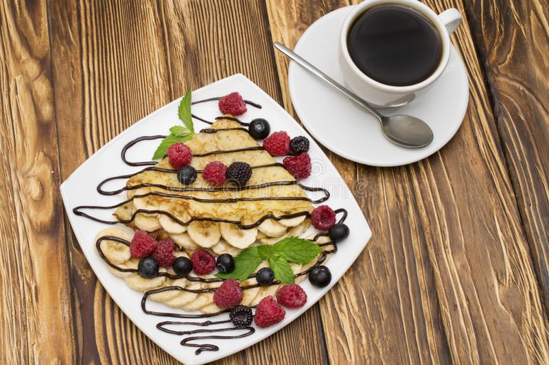 Homemade crepes served with chocolate cream, Banana, fresh blueberries, raspberries on a wooden background, pancakes.  stock photos