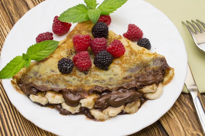 Homemade crepes served with chocolate cream, Banana, fresh blueberries, raspberries on a wooden background, pancakes.  royalty free stock images