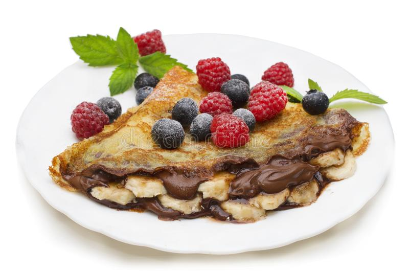 Homemade crepes served with chocolate cream, fresh blueberries and raspberries, powdered sugar on a white background.  royalty free stock photos