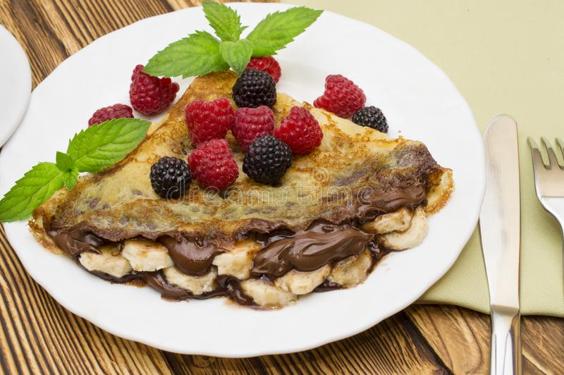 Homemade crepes served with chocolate cream, fresh blueberries and raspberries, powdered sugar on a white background.  royalty free stock photo