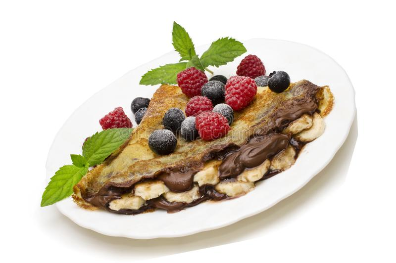 Homemade crepes served with chocolate cream, fresh blueberries and raspberries, powdered sugar on a white background.  stock images