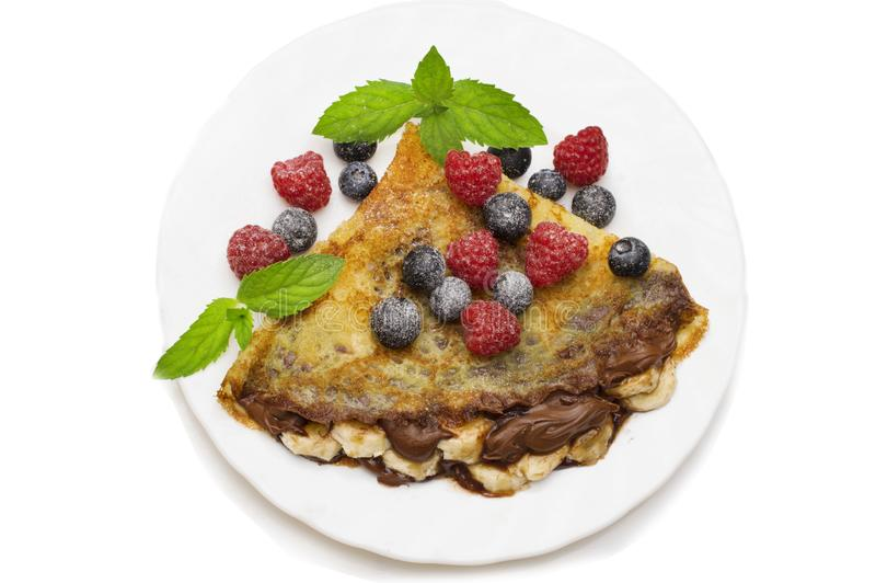 Homemade crepes served with chocolate cream, fresh blueberries and raspberries, powdered sugar on a white background.  stock photos