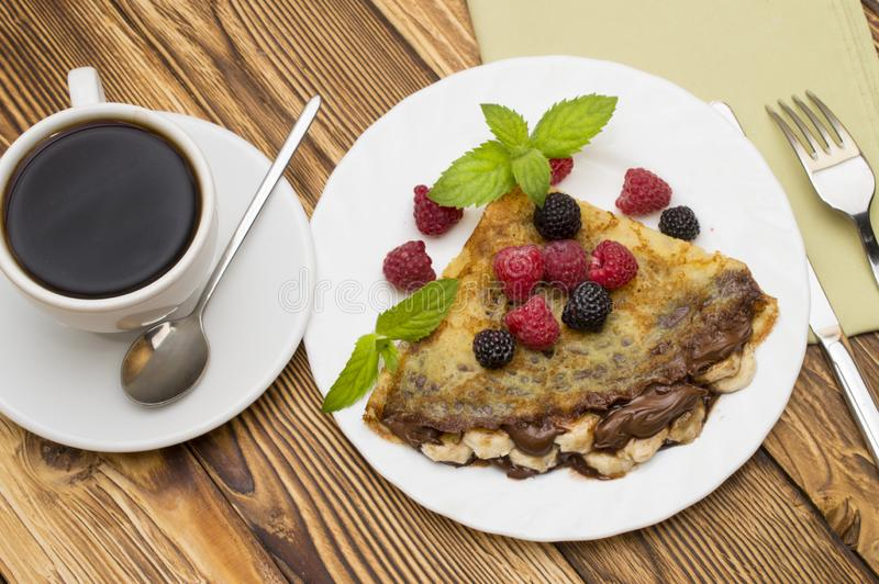 Homemade crepes served with fresh blueberries and powdered sugar on rustic wooden table.  royalty free stock image
