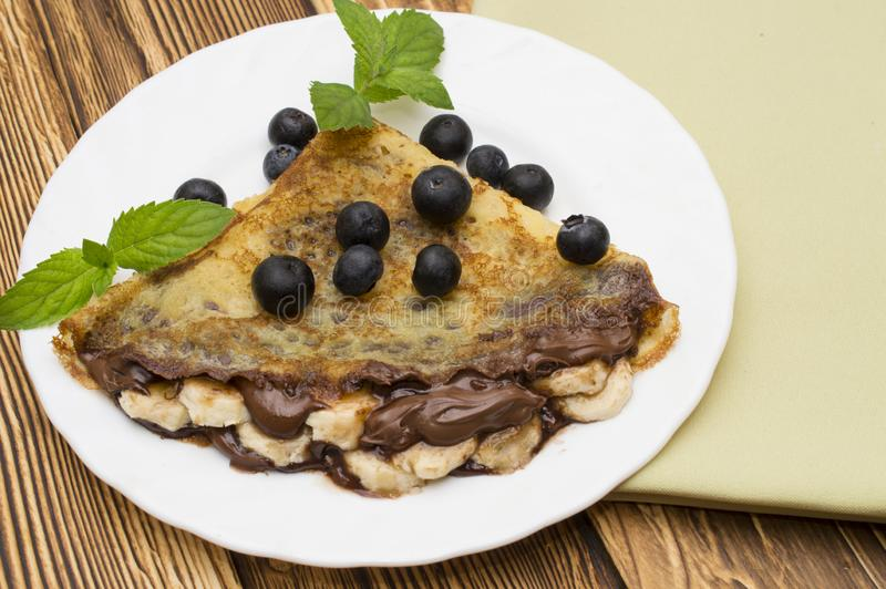 Homemade crepes served with fresh blueberries and powdered sugar on rustic wooden table.  royalty free stock photos