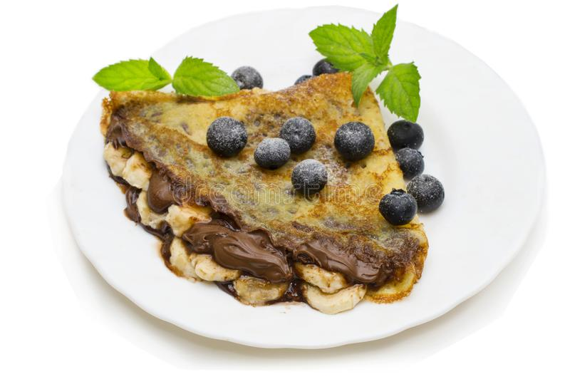 Homemade crepes served with fresh blueberries and powdered sugar on rustic wooden table in cast iron skillet.  royalty free stock photography