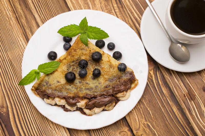Homemade crepes served with fresh blueberries and powdered sugar on rustic wooden table in cast iron skillet.  royalty free stock photos