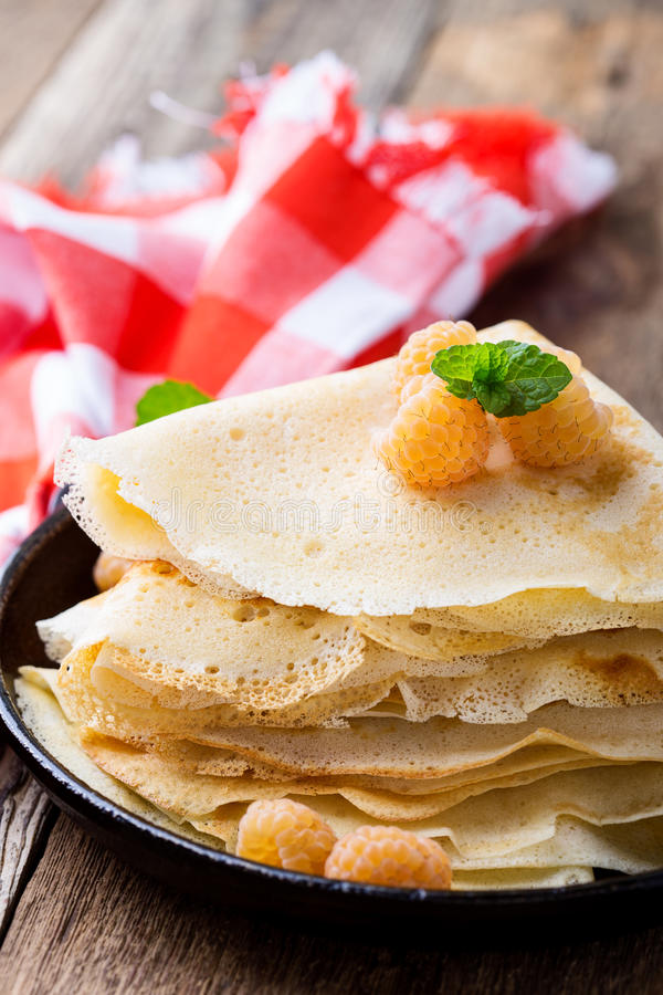 Homemade crepes served with fresh yelllow raspberries. In cast iron skillet for romantic brunch on rustic table witn red-checked tablecloth royalty free stock photos