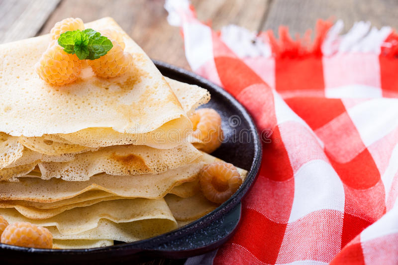 Homemade crepes served with fresh yelllow raspberries. In cast iron skillet for romantic brunch on rustic table witn red-checked tablecloth royalty free stock images