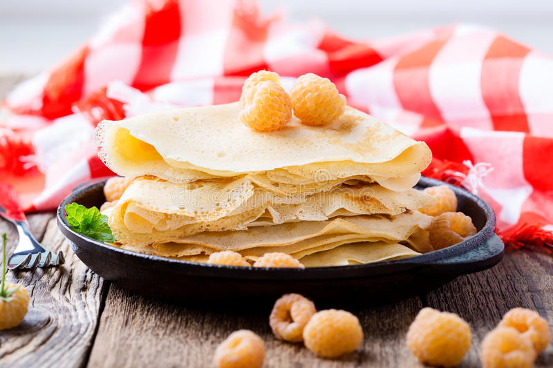 Homemade crepes served with fresh yelllow raspberries. In cast iron skillet for romantic brunch on rustic table witn red-checked tablecloth stock photo