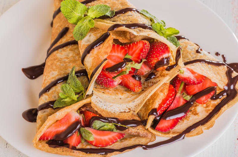 Homemade Crepes with strawberries and chocolate syrup. On a white background stock photo