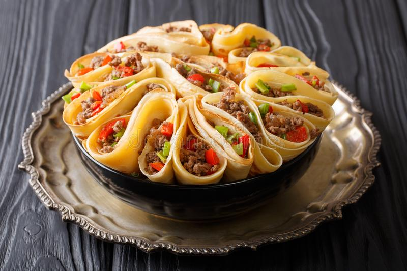 Homemade crepes stuffed with beef, peppers and onions closeup. h. Homemade crepes stuffed with beef, peppers and onions closeup on the table. horizontal stock photography