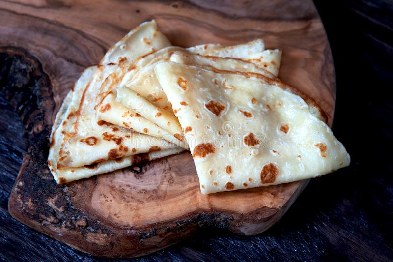 Homemade crepes, thin pancakes on a wooden board. Close up stock photos