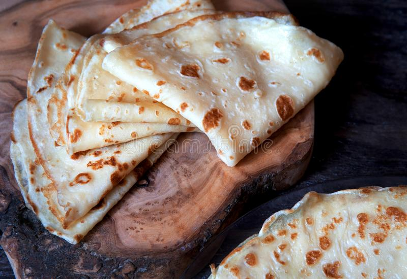 Homemade crepes, thin pancakes on a wooden board. Close up royalty free stock photos