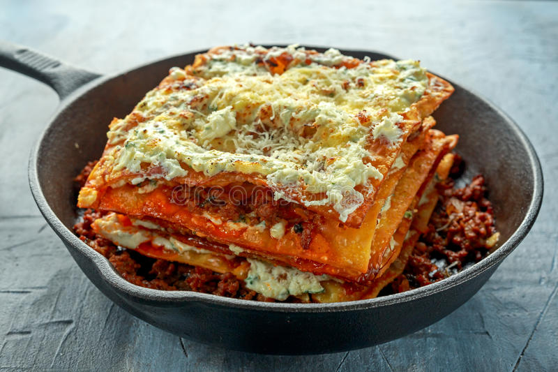 Homemade Crispy lasagna in iron pan with minced beef bolognese sauce, parmesan cheese.  stock photos