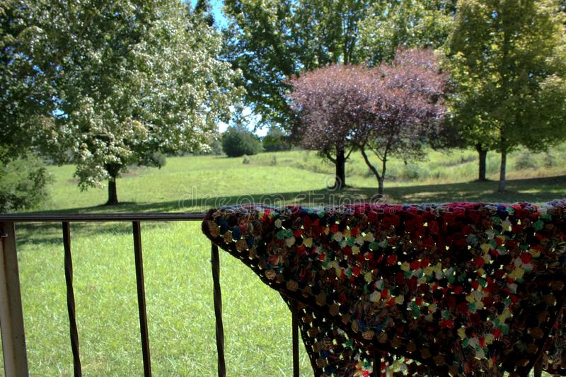 Homemade crocheted blanket on porch railing royalty free stock images