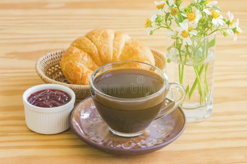 Homemade croissant on wood basket with black coffee and strawberry jam. Delicious and quick breakfast with fresh homemade royalty free stock photos