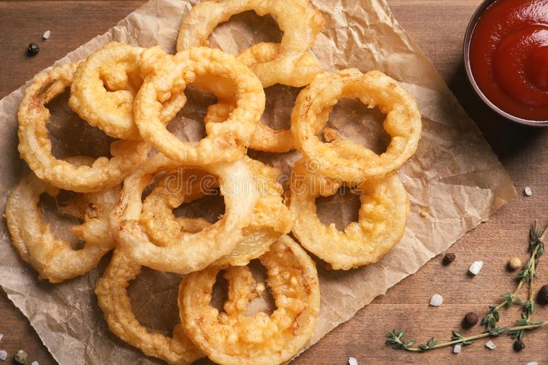 Homemade crunchy fried onion rings and sauce on wooden background. Top view royalty free stock photography