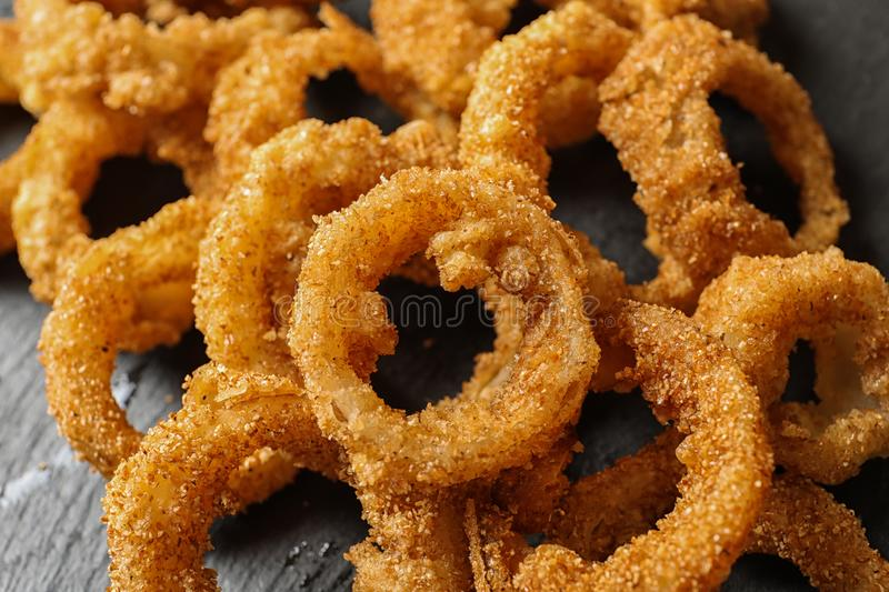 Homemade crunchy fried onion rings on slate plate. Closeup royalty free stock image