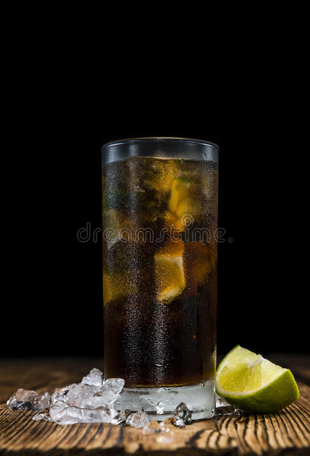 Homemade Cuba Libre. With fresh lime, brown rum and crushed ice on an old wooden table stock photography