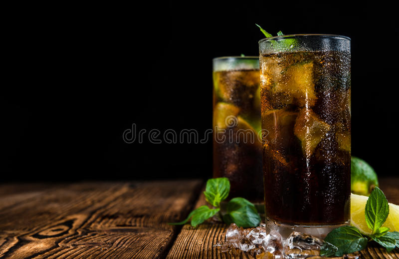 Homemade Cuba Libre. With fresh lime, brown rum and crushed ice on an old wooden table stock images