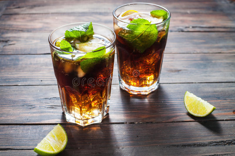 Homemade Cuba Libre with fresh lime, brown rum and crushed ice on an old wooden table royalty free stock image